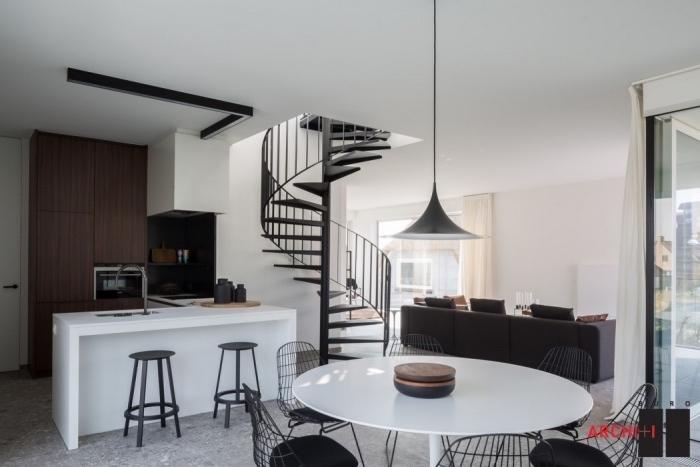 modele de petite cuisine équipée en bois avec ilot central blanc, coin salle à manger avec table basse blanche et chaises noires, escalier colimacon, salon avec canapé noir
