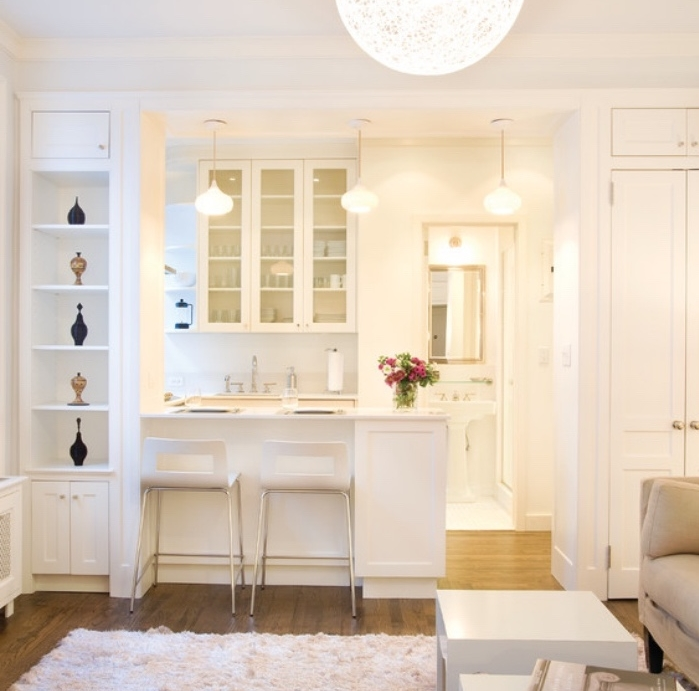 petite cuisine équipée avec meuble, ilot, facade cuisine blanche, parquet clair, canapé gris et table basses blanches, tapis blanc