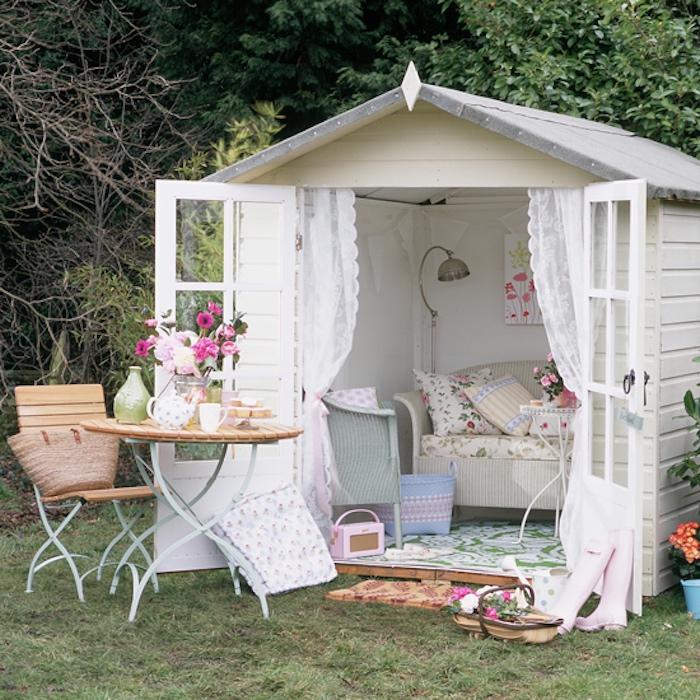 cabane de jardin, canap;e shabby chic et fauteuil vintage, maisonnette blanche, table et chaise en bois et métal, rideaux blanches, tapis vert et blanc
