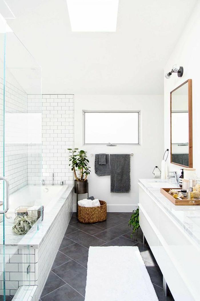 petite salle de bains avec baignoire et grand meuble en blanc pour le lavabo et pour ranger
