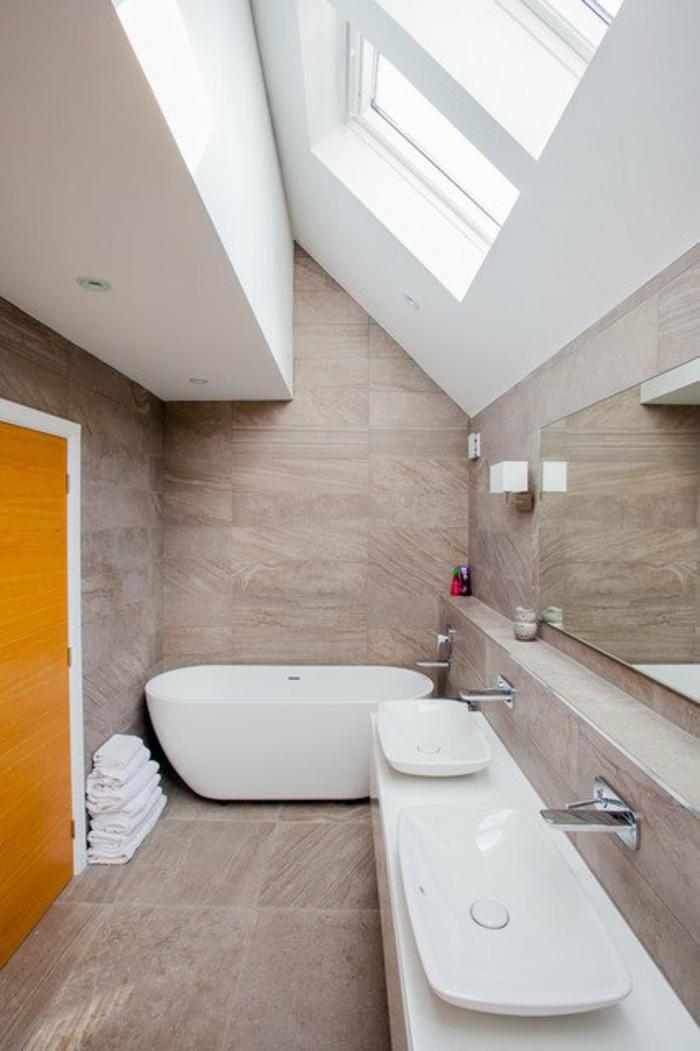 petit salle de bain avec toit sous pente baignoire blanche avec deux lavabos blancs ovales