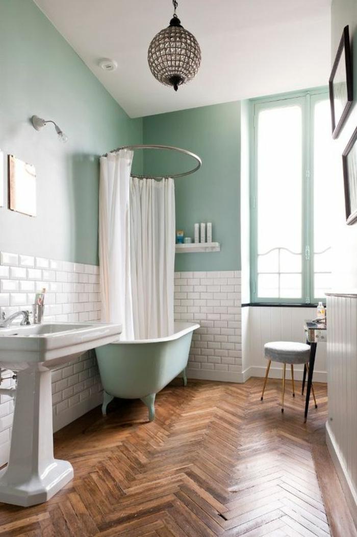 salle de bain petite avec baignoire vert pistache et rideaux blancs sur métal en forme ronde au dessus de la baignoire