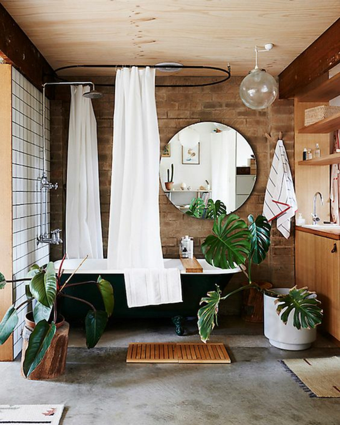 petites salles de bain avec baignoire noire et miroir rond rideaux douche blancs