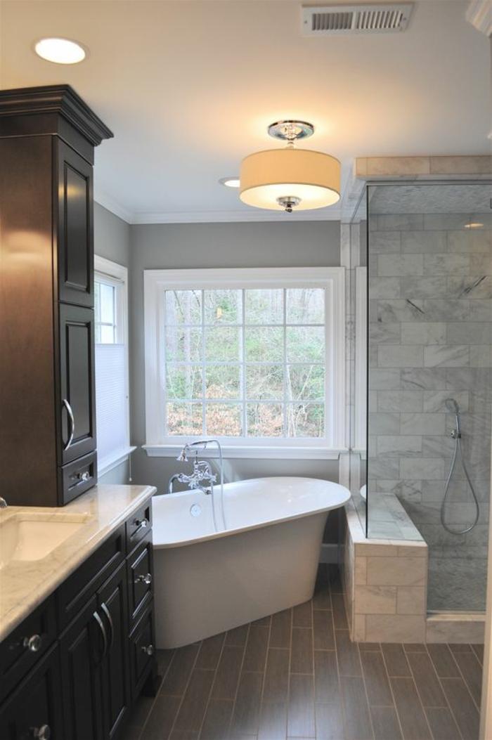 salle de bain petite baignoire installée dans un angle et luminaire rond suspension courte