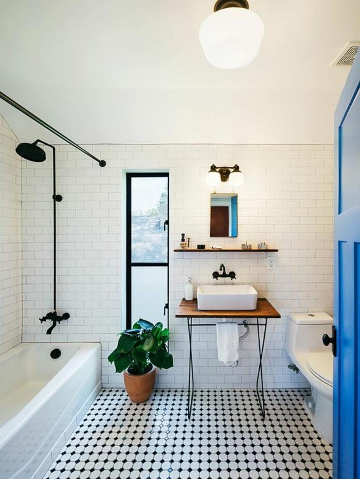 petit salle de bain avec baignoire et des briques en blanc avec porte bleu intense