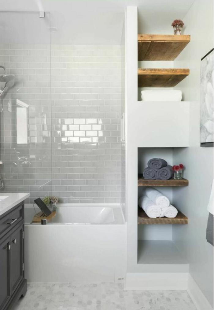 petite salle de bain aux étagères en bois marron clair avec des murs motifs briques blanches