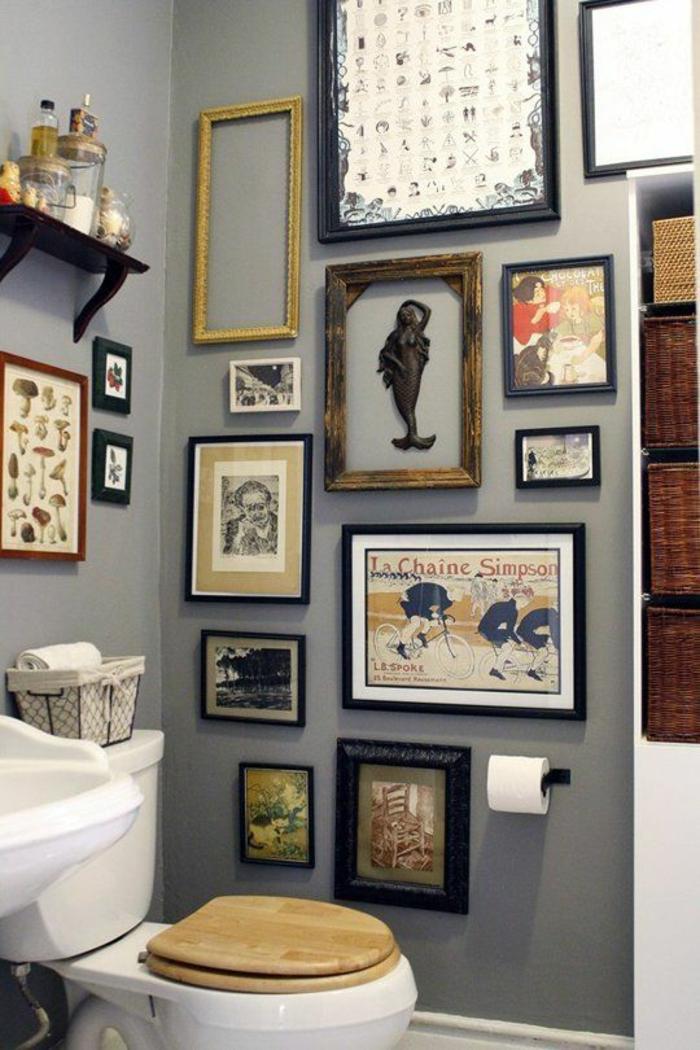 petite salle de bain au mur gris décoré de beaucoup de tableaux et des corbeilles en rotin tressé pour le rangement