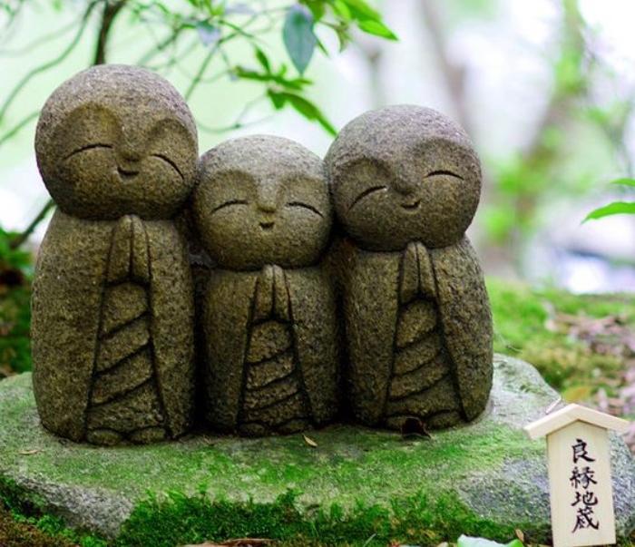 trois petites statuettes japonaises en train de faire la prière sur une pierre, recouvert de mousse, decoration zen sympa