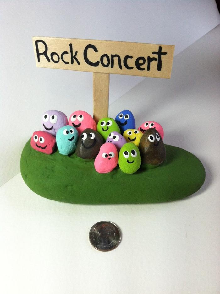 un arrangement original de petits galets peints aux couleurs différents posés sur une grande pierre, déco amusante qui joue sur les mots