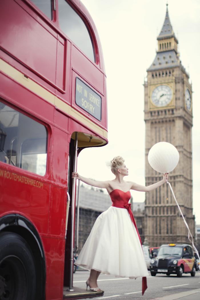 une photo mariage artistique de la mariée montée sur un bus anglais vintage