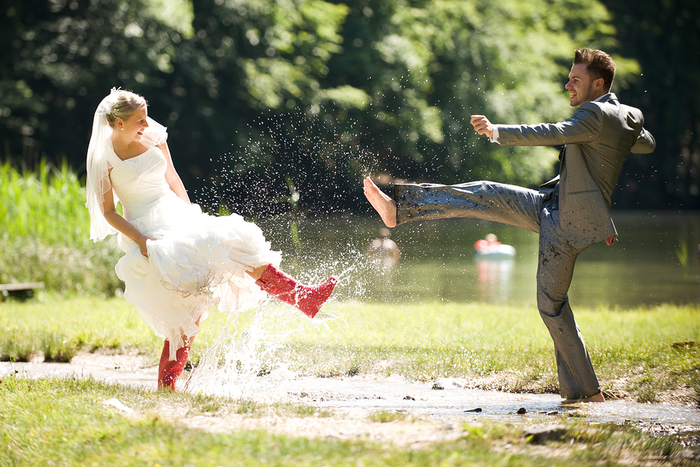 une séance photo originale de couple de marié qui s'amusent à s'éclabousser dans la flaque