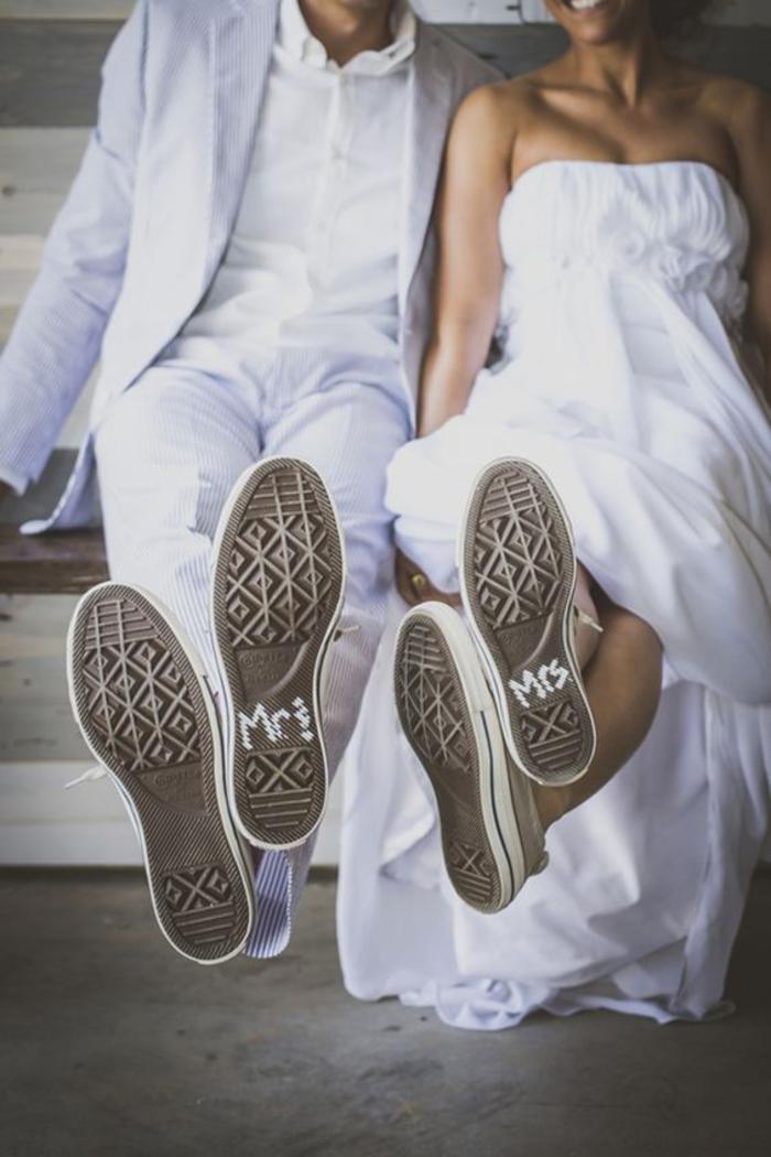 photo de couple décontracté avec leurs baskets de mariage en premier plan