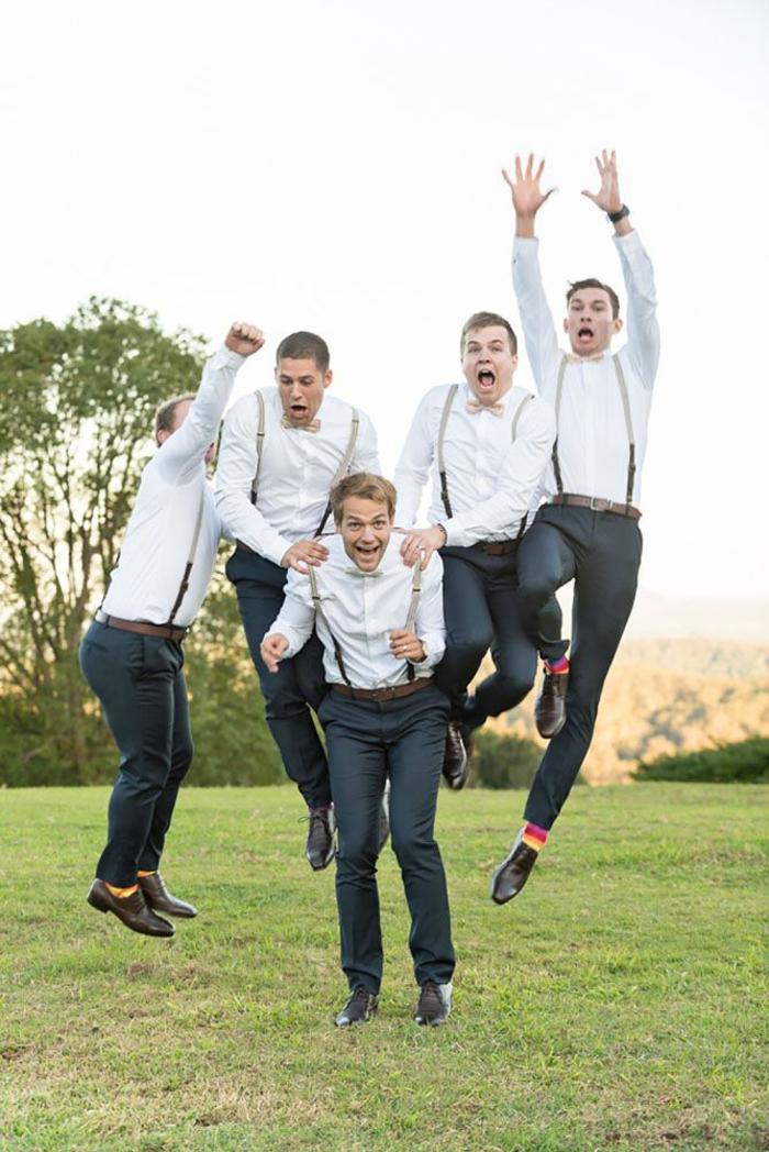 une photo originale de marié et ses témoins de mariage sautant dans l'air, séance photo insolite dans la nature