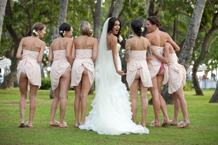 une photo mariage de groupe rigolo avec la mariée et les demoiselle d'honneur, robes coincées dans les culottes