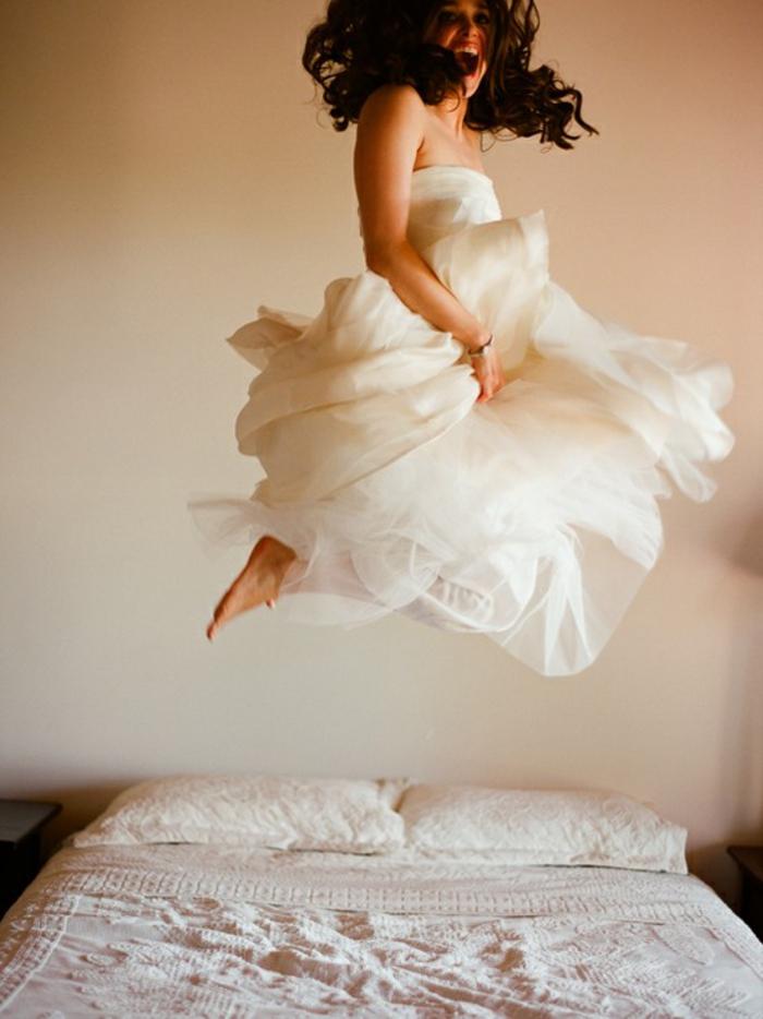 séance photo de boudoir originale, photo artistique de la mariée en train de sauter sur le lit