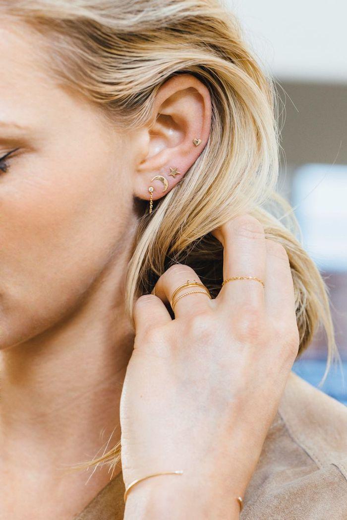 piercing oreille, bijoux en or, cheveux blonds, blazer beige, piercing femme, boucles d'oreille coeur