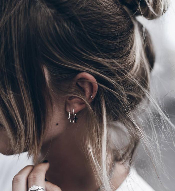 piercing conch, chignon décontracté, petit anneau pour l'oreille, manucure noire, bague en argent