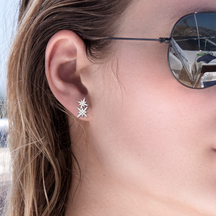piercing oreille, cheveux balayage californien, boucles d'oreilles étoiles, lunettes de soleil noirs