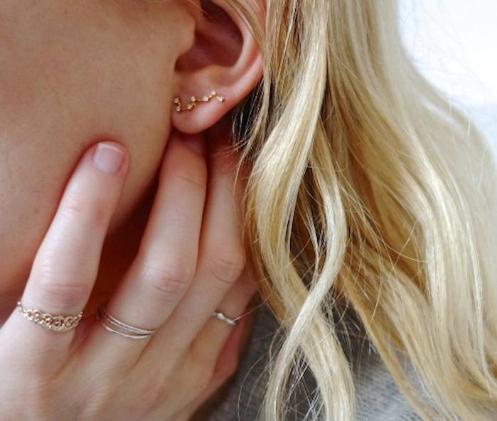piercing femme, blouse grise, coloration blonde, cheveux longs, bagues femme, piercing constellation étoiles
