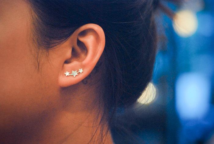 piercing femme, bijoux constellation étoiles, piercing discret femme, chignon haut, cheveux noirs