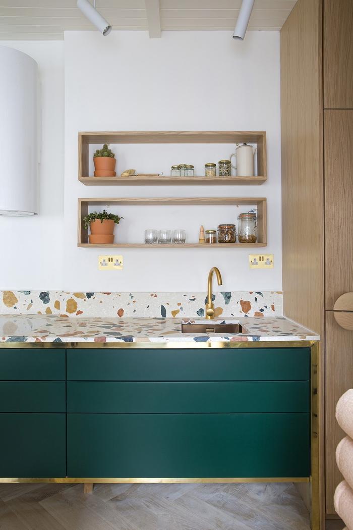 cuisine vert canard et blanc au design épuré, un plant de travail aspect terrazzo qui se marient parfaitement avec la couleur du bois clair et les placards de cuisine