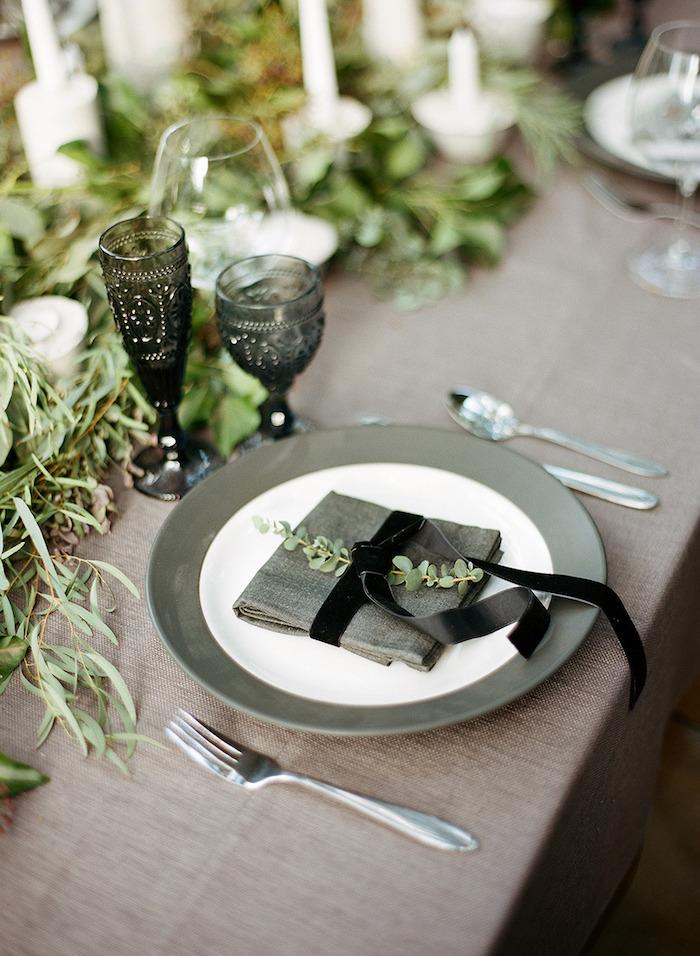 nappe de table grise, couverts de table, assiette vert et bleu, pliage de serviette avec ruban noir