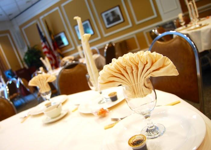 déco de table avec serviette origami, serviette blanche en forme de bougie, service de table blanc