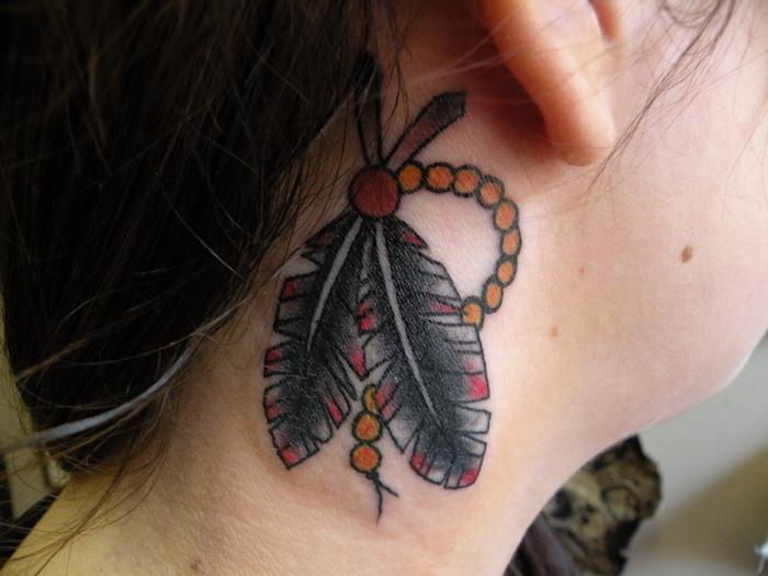 idée tatouage femme, cheveux marron foncé, tatouage en design plume amérindienne, art corporel en couleurs