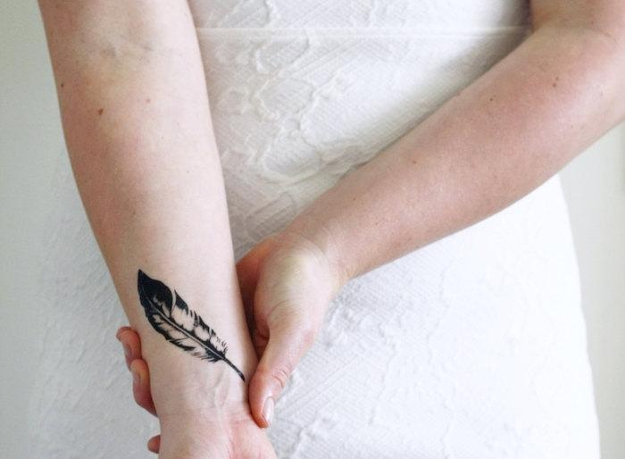 tatouage femme, dessin en encre sur la peau, tatouage sur le poignet à design plume
