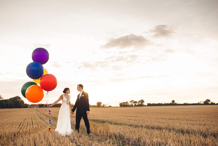 photo de couple poétique dans les champs d'automne, contraste entre les couleurs d'automne et les ballons colorés