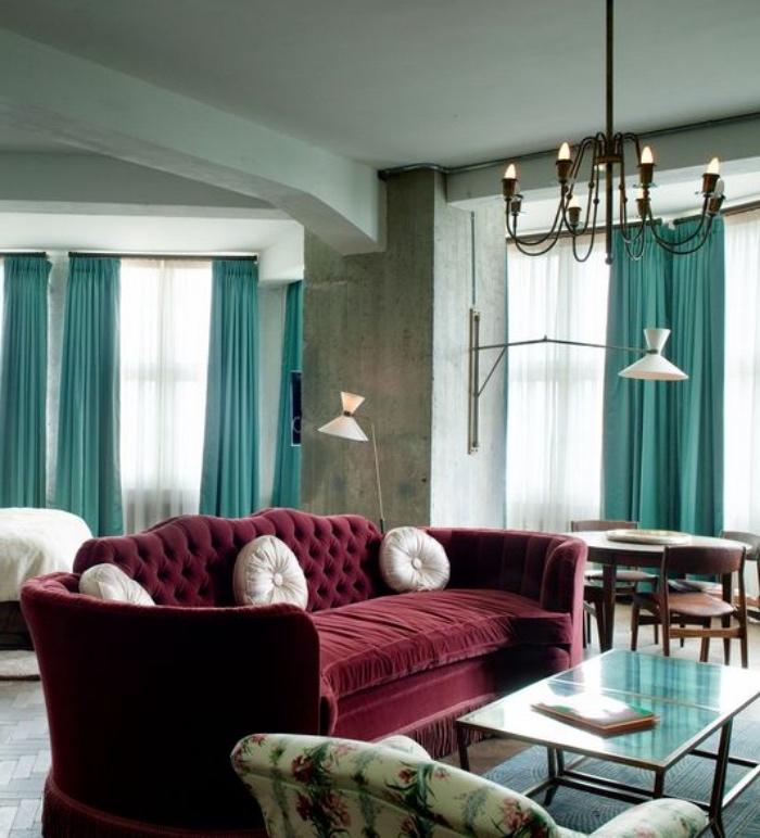 mur couleur gris anthracite, grand canapé bordeaux, table basse, fauteuil à motifs floraux, rideaux bleu canrd et lustre élégant