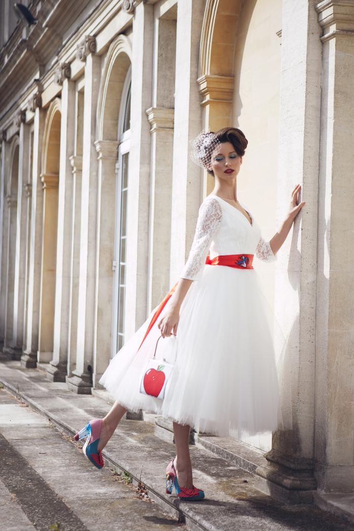 une robe de mariée vintage cintrée, coiffure année 50 accessoirisée avec une voilette rétro