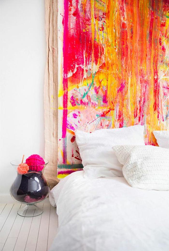 couleur magenta couleur fushia sur un panneau decoratif au dessus du lit dans une chambre a sol imitation bois clair