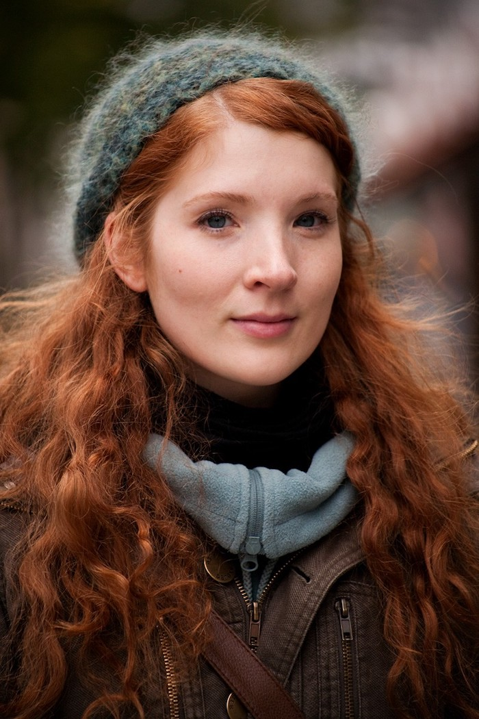 couleur cuivre, cheveux frisés et longs en orange, bonnet bleu modèle femme, manteau marron, pull over noir femme