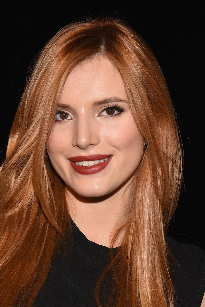 cheveux roux, robe noire sans manches, maquillage avec eye-liner noir et rouge à lèvres marron, fond de teint pêche