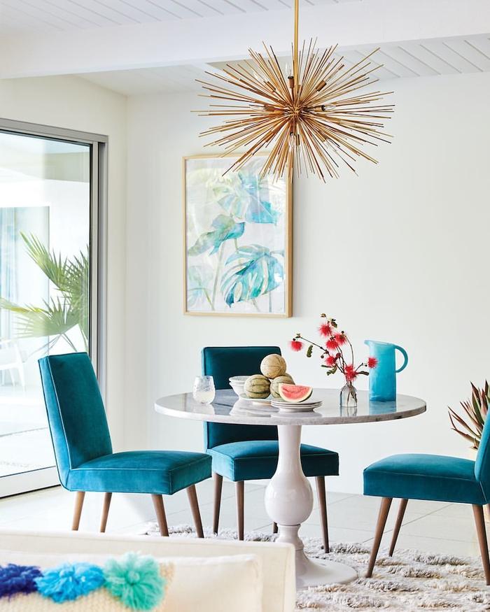 salon blanc moderne illuminé par la couleur bleu sarcelle sur les chaises
