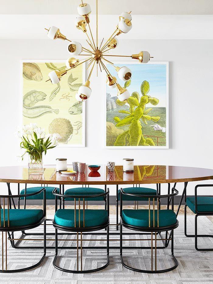 une salle à manger colorée de style rétro chic avec une grande table ovale à finition laquée et des chaises bleu paon