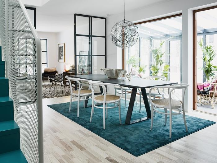 une salle à manger scandinave conviviale et lumineuse, tapis bleu paon qui délimite le coin repas