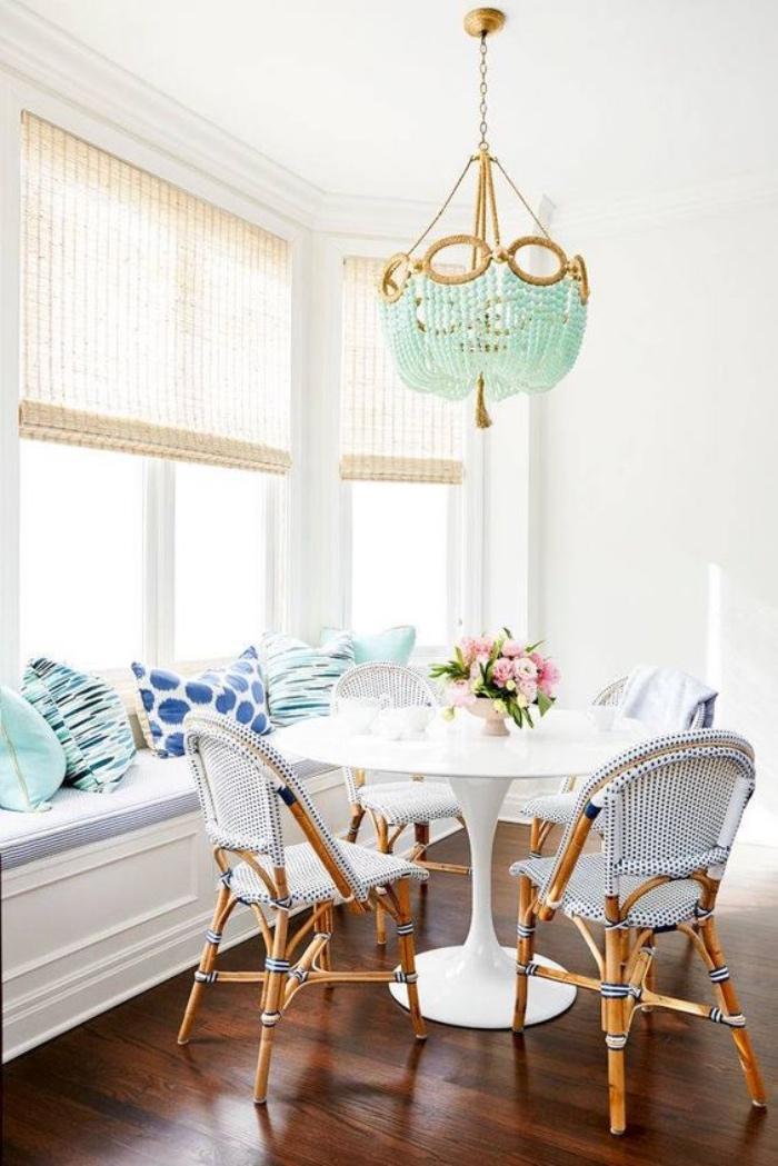 salle a manger blanche, table blanche et chaises en bois et tissu canapé blanc, coussins et lustre vert mint, bouquet de fleurs
