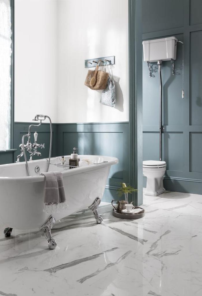 une salle de bain élégante et sophistiqué au sol effet brillant avec lambris peint en couleur canard