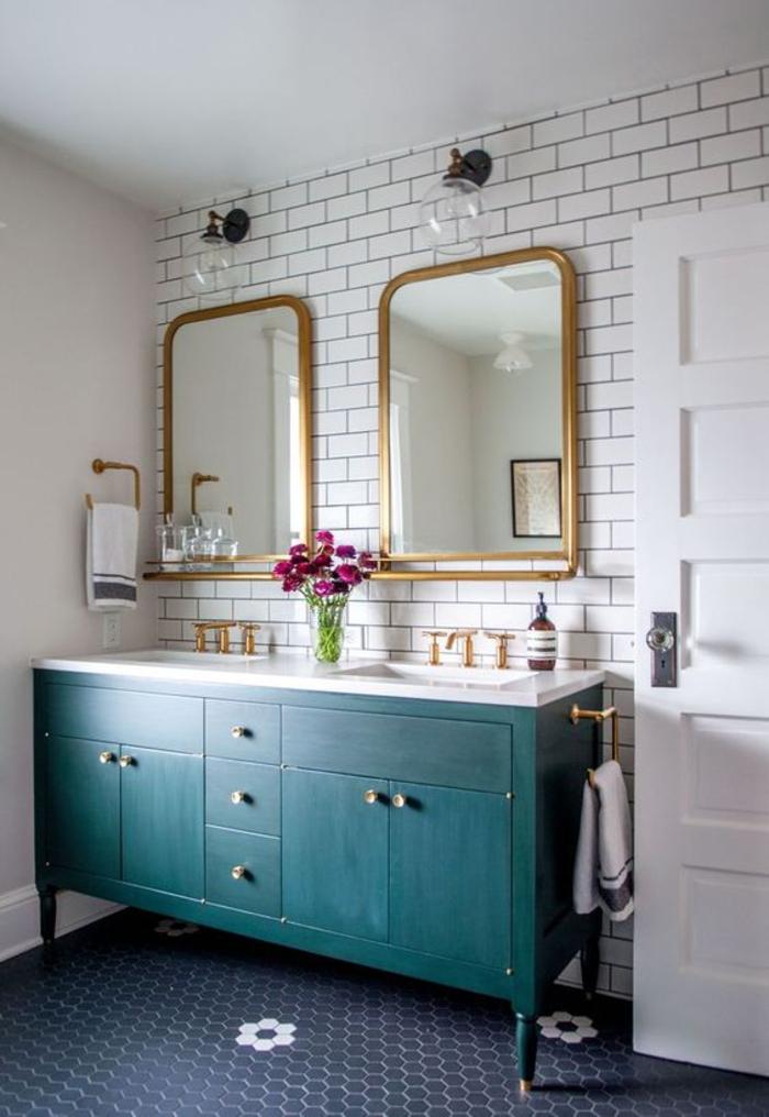 une salle de bain classique sublimée par un carrelage métro, des appliques industrielles et des cabinets bleu paon
