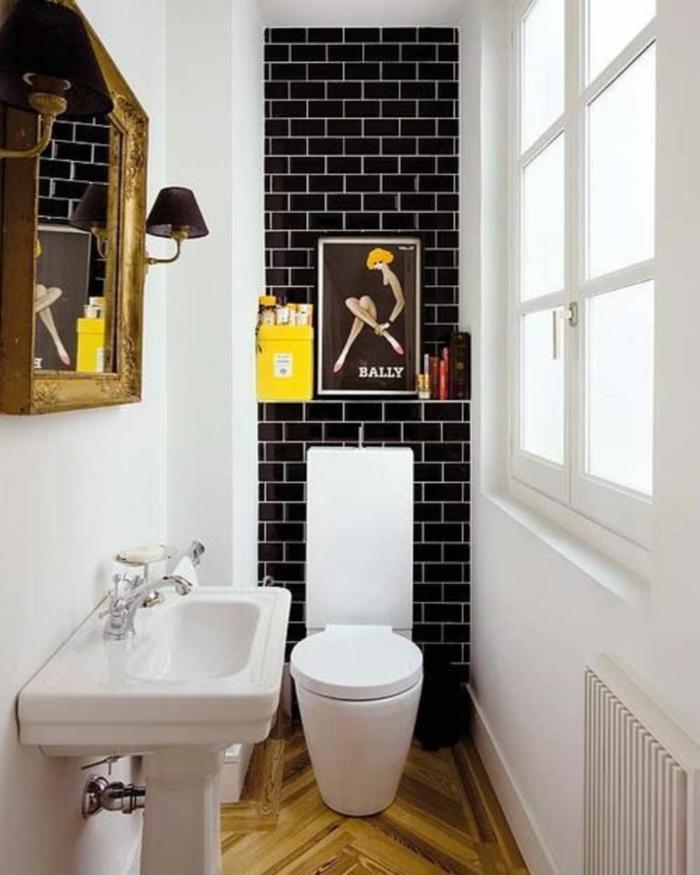 petite salle de bain aux briques noires autour du meuble WC et aux murs en blanc avec grand miroir vintage au cadre doré