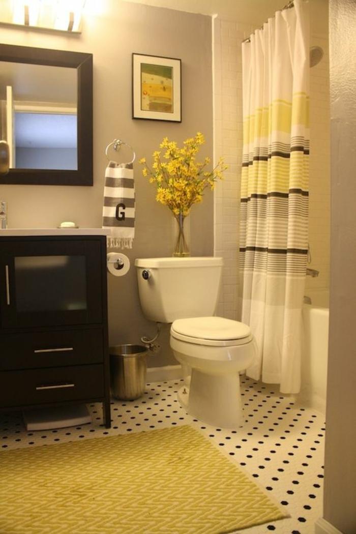 petite salle de bains avec rideaux blancs aux rayures jaunes et marron avec tapis jaune meubles noirs