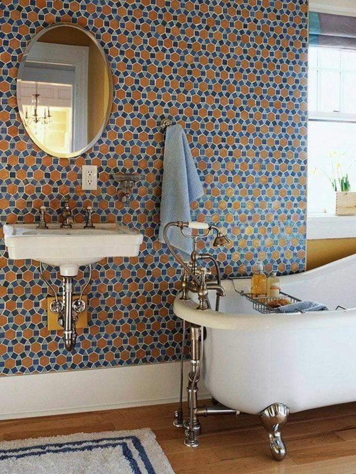 petite salle de bain aux murs en ruches bleues et oranges avec miroir rond