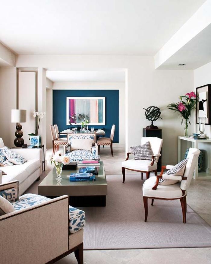 salon élégant en blanc dynamisé par un mur d'accent bleu paon, effet de profondeur