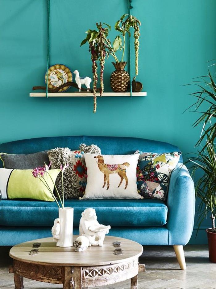un joli canapé bleu paon en velours mis en valeur par les coussins ethniques disparates et déco exotique