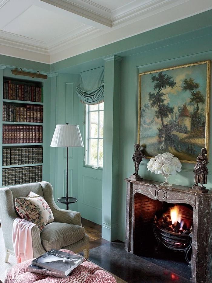 salon vert d eau vintage, cheminée en pierre romantique, fauteuil gris, bibliothèque, vieux bouquins, tableau paysage au dessus de la cheminée