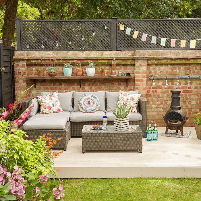 aménager son jardin avec un salon de jardin tressé, canapé et table avec plateau en verre, coussins colorés style boheme, cheminée extérieur, pelouse verte et parterre de fleurs
