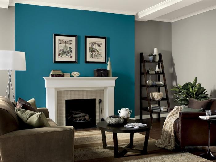 salon moderne aux nuances de marron, taupe et bleu paon, pan de mur bleu qui délimité une cheminée traditionnelle