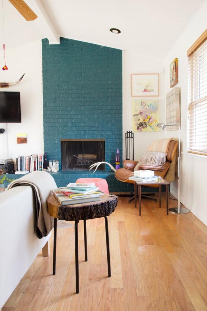 coin de détente cosy dans un salon style scandinave, cheminée moderne délimitée par un mur en briques vert canard